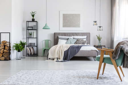キングサイズのベッドの毛布とスタイリッシュなホテルの部屋に立っているミントの椅子が 2 脚