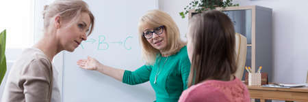 Female elegant psychotherapist suggesting problem solution to mother and daughter