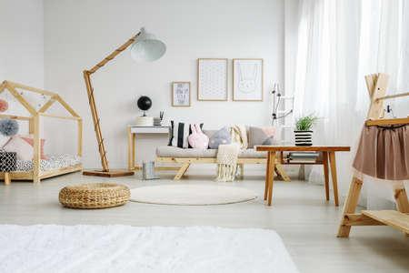 スタイリッシュな北欧の楽しい装飾的な枕を持つ少女の寝室