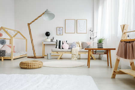 Stylish scandinavian fun bedroom of girl with decorative pillows