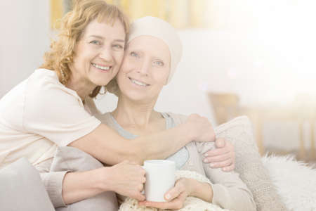 Woman with scarf and her supportive sister fighting cancer together Stock Photo
