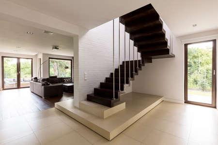 Escalier dans le couloir avec un séjour en arrière-plan Banque d'images - 83598941