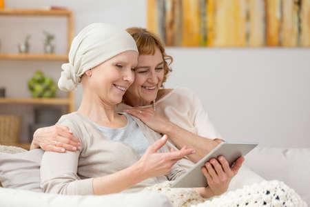 Vrouw met kanker en haar vriend kijken naar foto's op tablet