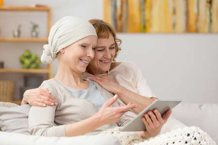 Woman with cancer and her friend looking at photos on tablet