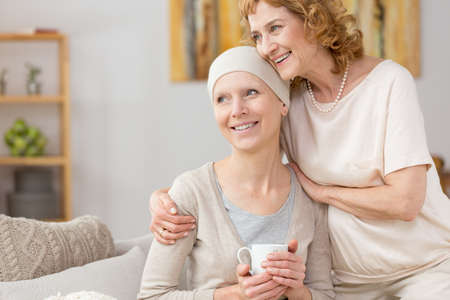 Happy woman with scarf struggling with illness with her moms help Stock Photo