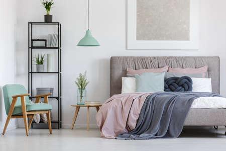 Groot bed met schattig pastel beddengoed in de kamer van de vrouw Stockfoto