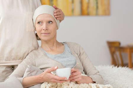 Zieke vrouw die aan kanker lijdt die thee en het ontspannen drinkt Stockfoto