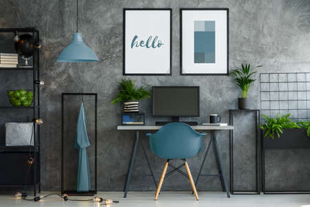 Stylish turquoise and gray interior with desk and mock-up posters