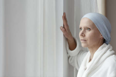 Depressed woman with blue scarf struggling with cancer alone