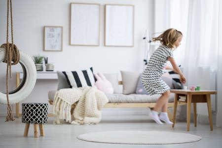Blond meisje in jurk springen in moderne kamer met schommel Stockfoto