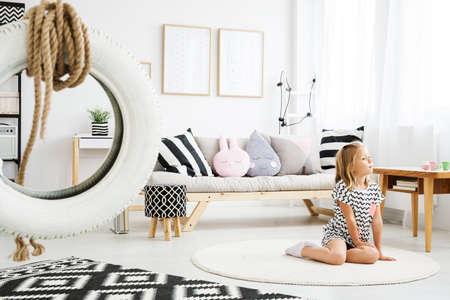 트렌디 한 스칸디나비아 화이트 방에 바닥에 앉아있는 어린 금발 소녀