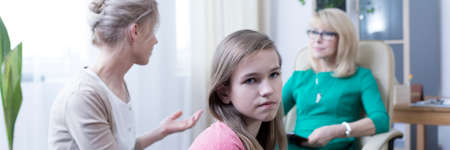 Offended withdrawn teenage girl during therapy with her mother Stock Photo