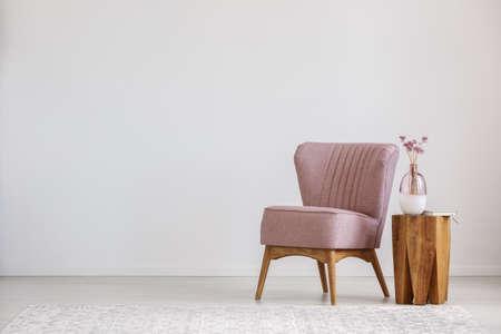 Bonitos rosa flores em vaso de vidro colocado na mesa de madeira em pé por pequena cadeira Foto de archivo - 83335339