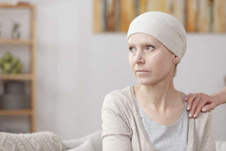 Sad sick woman with lung cancer sitting at home with friend Foto de archivo