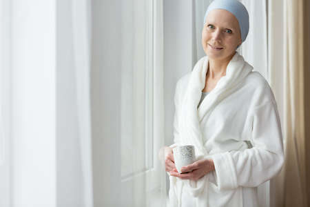 Smiling sick woman in bathrobe drinking morning coffee at home Stock Photo