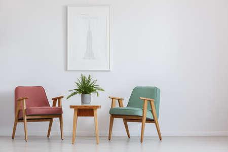 Salle d'attente avec deux fauteuils et une affiche suspendue au-dessus d'une petite table Banque d'images - 83573649