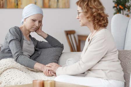 Besorgte Frau mit blauem Schal auf dem Kopf über Krebs Rückfall denken Standard-Bild - 83573655