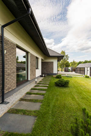 Elegant detached house exterior with brickwall and big garden