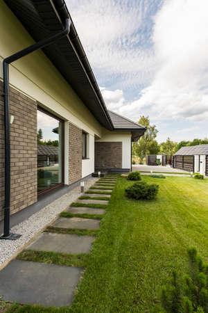 Maison individuelle élégant à l & # 39 ; extérieur avec le ciment et grand jardin Banque d'images - 83335061