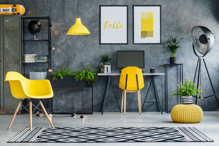 Study space with concrete walls and yellow and metal furniture