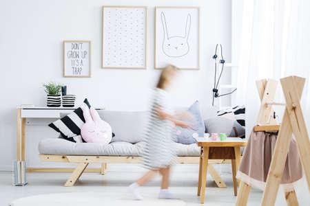 코트 랙과 현대 아늑한 방 주위를 산책하는 흰 드레스 소녀