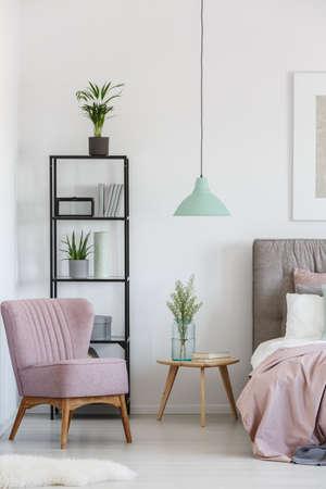 Zwart metalen rek met potplanten en boeken in de hoek van de slaapkamer