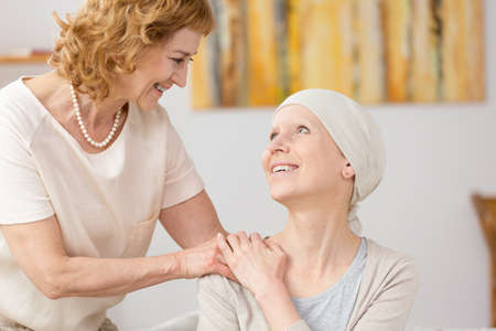 Happy senior woman holding her suffering from cancer friends arm Stock Photo