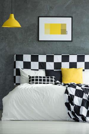 검은 색, 흰색 및 노란색 베개가있는 킹 사이즈 침대 위의 노란색 램프 스톡 콘텐츠