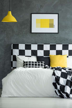Yellow lamp above king-size bed with black, white and yellow pillow Stok Fotoğraf