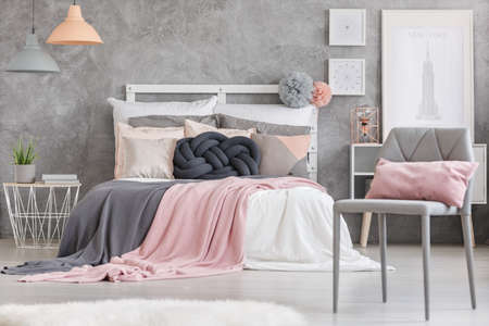 bedside: Gray chair with small pink pillow standing in a room with king-size bed Stock Photo