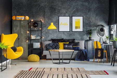 Freelancers room with gray concrete wall and vibrant yellow accents