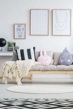 View of wooden nordic sofa in trendy childrens room Zdjęcie Seryjne