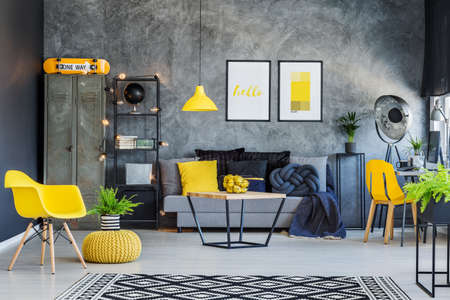 grey rug: Creative office interior with gray couch, yellow accents and metal furniture Stock Photo