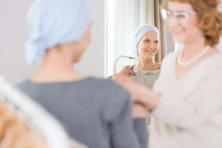 Sick woman suffering from cancer and her friend picking new outfit Stock Photo