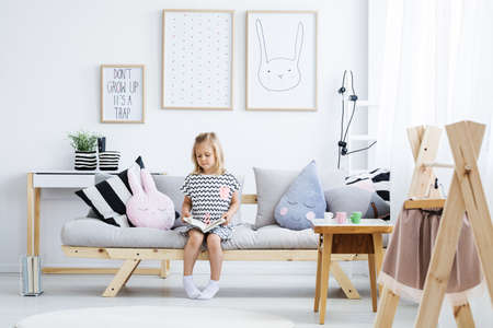 Cute young girl reading book on stylish sofa in white room