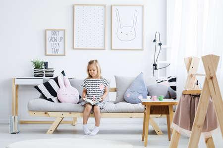 Leuk jong meisje lezen boek op stijlvolle bank in witte kamer