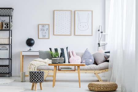 装飾的な枕が付いている簡単なソファーとパステルの乙女チックな部屋 写真素材 - 83313484