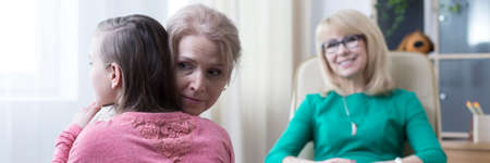 Adolescent girl and middle-aged woman hugging during psychotherapy