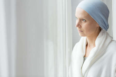Worried woman with cancer wearing blue scarf and white bathrobe