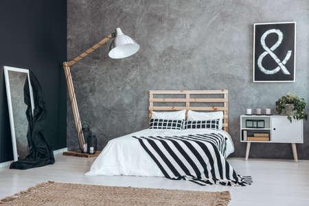 デザイン木製ランプに純黒の壁に白いフレームが付いているミラーが傾いています。 写真素材