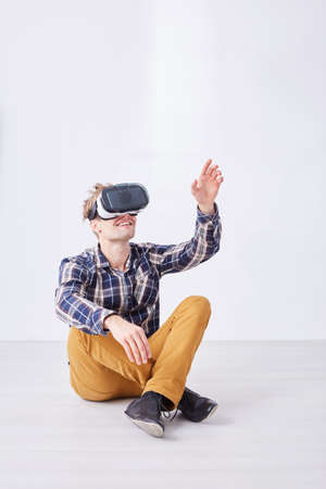 Man plays funny game with expanded reality using glasses while sitting in white empty room Stock Photo
