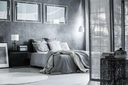회색 침실 장식, 방 분할기 및 미니멀리스트 가구가있는 스칸디나비아 아파트 스톡 콘텐츠