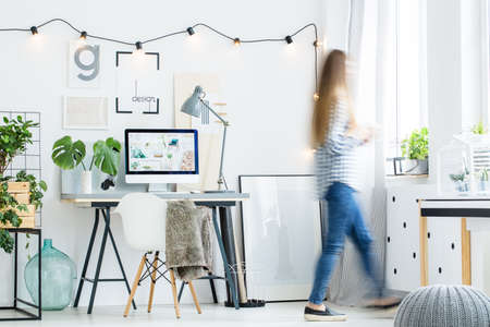 home office interior: Person with long hair walks in office room in nordic style with grey pouf on floor Stock Photo