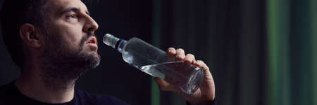 Sad man drinking alcohol from glass bottle, panoramic view Stock Photo