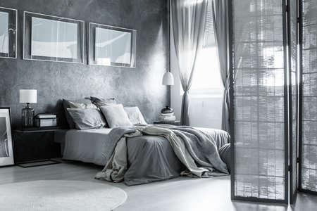 Camera da letto accogliente bianca e grigia con accessori e poster semplici Archivio Fotografico