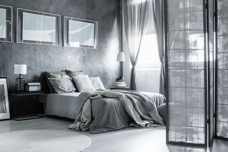 White and gray cozy bedroom with simple accessories and poster Reklamní fotografie