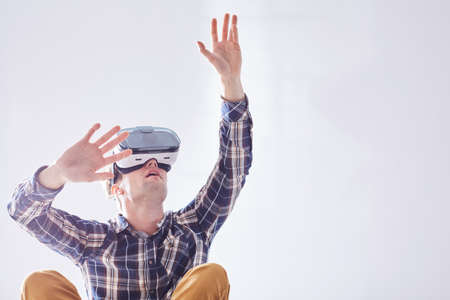 Excited man uses new technologies to have fun in virtual reality in white room Banco de Imagens