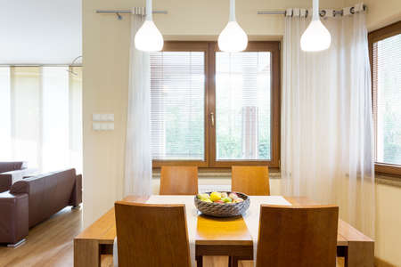Cozy modern designed dining hall with wooden table and chairs. On the left living room