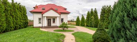 Vista de la casa unifamiliar con un cuidado césped y setos Foto de archivo - 83595396