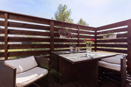 Mooie patio met bloemen en houten meubilair
